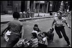 Police officer playing with the children in Harlem, 1970s.   From a series on the New York Police Dept in the 1970s, shot by Leonard Freed / Magnum Photos.