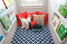 Nautical kids' book nook situated under dormer window fitted with a seat cushion made in Serena and Lily Diamond Fabric in Navy accompanied by red pillows, a tasseled pillow and an embroidered Hawaii Pillow flanked by walls painted Benjamin Moore Gray Owl which frame Land of Nod Straight & Narrow Book Ledges.