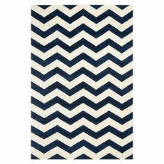 "Showcasing a timeless chevron motif in dark blue and ivory, this hand-tufted wool rug brings visual interest to your dining room or den.  Product: RugConstruction Material: 100% WoolColor: Dark blue and ivoryFeatures:  Made in IndiaHand-tuftedCotton backing Pile Height: 0.5"" Note: Please be aware that actual colors may vary from those shown on your screen. Accent rugs may also not show the entire pattern that the corresponding area rugs have.Cleaning and Care: Professional cleaning ..."