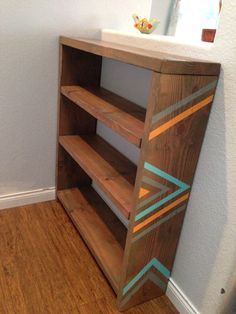 Wooden bookshelf, arrows and chevrons painted on the side.