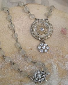 Pendant is 2 inches long incorporating antique rhinstone jewelry, a vintage glass button, antique dictionary page, and vintage rhinstone button drop. The beaded chain is from an antique glass pearl chain with the pearling removed with a new attached rhinestone clasp.