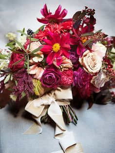 Florist Bridget Vizoso created Daisy's sumptuous bouquet, which included garden roses, red nerines, Euphorbia fulgens, dahlias, and cosmos nestled amid fall foliage and berries.
