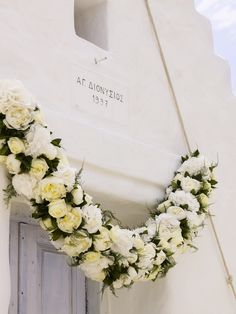 A garland with peonies, roses and hydrangea at the top of the church's door http://www.instyle.gr/photo-gallery/gamos-se-nisi-aplos-ke-entiposiakos-stolismos-gia-mia-paradosiaki-teleti-stin-ekklisia/id/1/
