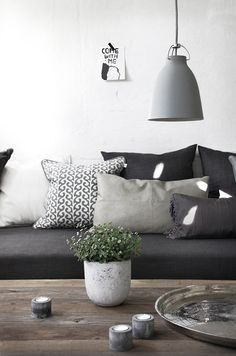 Love the different shades of grey with the dark grey couches, and the little pop of green and white