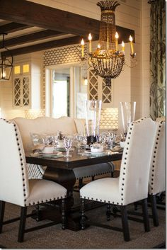 white and black dining room with white tufted chairs, black table and chandelier
