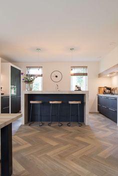 Natuurlijke materialen in een perfecte combinatie van een zwart houten fronten en houten details. Een heerlijke sfeer in deze leefkeuken met een prachtige combinatie van stijlvol witte stollen om de keuken.