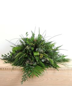 A beautiful casket spray of greenery. This display uses a mixture of seasonal tropical foliages.