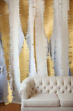 Fringed crepe paper rolls in metallics and neutrals, twisted from ceiling to floor. Photo booth backdrop?