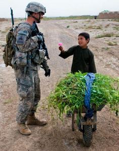 An afghan child offers a flower to U.S. Army Sgt.
