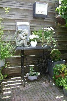 Rincón con una máquina de coser rodeada de plantas