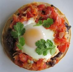Huevos Rancheros: Eggs poached in salsa, on a tostada with refried beans. Que Rico!   recipe from hilahcooking.com