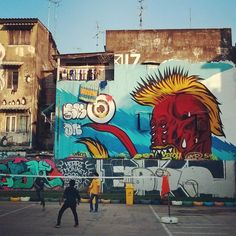 Locals play sepak takraw in front of street art in Bangkok, Thailand