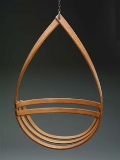 "A hanging chair, composed of a bentwood slat shaped into a teardrop form, with two curved slats placed horizontally to form the back, to which are joined two additional curved slats forming the seat. The chair is suspended by an iron hook and chain at the top of the ""teardrop."""