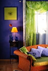 This room has a secondary color scheme because of the purple walls and pillows, green curtains, and orange couch and lamp.