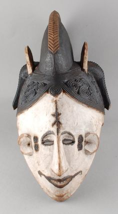 Mask; carved of wood; in the form of human face with large ridge running front to back, two prongs (painted white) on either side of ridge, braid of hair between each set of prongs; face painted white.