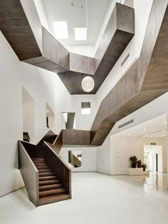Angular Stairway Stores - an experiment with angles and light casting. The geometric style is very contemporary especially set against the pure white glossy environment combined with the deeper, natural tones of the wooden stairs