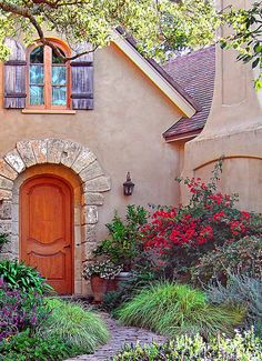 Entrance garden - curves and plantings that mirror the structure and colors of the cottage.  Lovely!