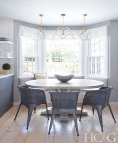 Modern Coastal Style oval dining table in kitchen with bay window and modern lighting Kitchen Banquette, Dining Nook, Dining Table In Kitchen, Dining Room Design, Dining Room Furniture, Oval Dining Tables, Furniture Design, Dining Chairs, Wicker Chairs