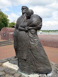 Kampen -  IJsselkade nabij Buitenhaven. 'Schokkermonument' (1991, brons), van de Ierse beeldhouwer Norman Burkett. Het  is een beeld van een schokker echtpaar, en werd op vrijdag 6/9/1991 onthuld op de plaats waar de Schokkers 132 jaar geleden aan wal zijn gegaan. Foto: G.J. Koppenaal, 31/5/2016.