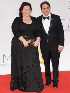 Emmys 2012: Melissa McCarthy  is wearing a dress co-designed by herself and Daniele Kurrle, a Burberry bag, Chopard jewels, and her daughter's ring.