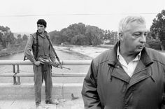 An Israeli soldier keeps his finger on the trigger of his assault rifle while Sharon (right) stands on the bridge overlooking the Awali Rive...