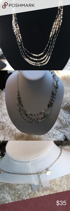 Mid length layered necklace, never worn Stylish 4 strand necklace to dress up or down any solid dress or top. Never worn .Crystals, black, white clear and silver, silver liquid spacers, length at longest is 22, with back extension chain. White House Black Market Jewelry Necklaces