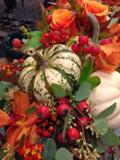 Fall Arrangement : Use of variegated gourds or pumpkins with berries & leaves...beautiful.