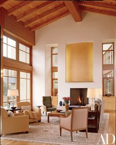 """Because of the view,"" says designer Audrey Alberts, ""the interiors could not be jarring in any way."" Architectural colorist Tina Beebe created the sculptural wall above the fireplace. Armchair, ceramic lamps and wing chair leathers, Kneedler-Fauchère. Armchair fabric, Great Plains. Rogers & Goffigon lounge chair and armchair pillow fabrics. Glass lamp, round table and low table, Holly Hunt."