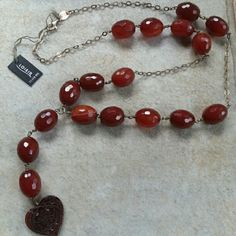 Sterling Silver and Carnelian Necklace This fabulous fall necklace contains 17 faceted Carnelian egg beads, 17-18 mms each. The carved heart measures 25mm X 26mm It is 28 inches in length ~ with 4 1/4 inch vertical It weighs about .25 lbs...I know that doesnt seem like a lot but it does have weight to it. It is stamped with both Sterling (.925) and German Silver  (.938)  This necklace makes quite a statement!   Thanks for looking! Bundle and save 15% ♡ Loisir Jewelry Necklaces