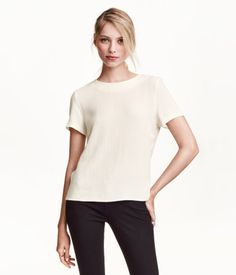 Short-sleeved blouse in woven, crêped fabric with a visible zip at back of neck and slightly longer back section.