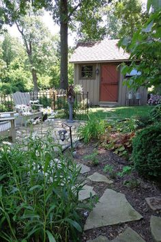 Idyllic Forest Shed  With a relaxing patio, an inviting birdhouse, and a cozy cover of vibrant green foliage, this little garden space could not be more idyllic. Check out the farm-inspired detail of those antique watering cans near the door!