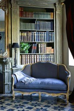 Dusky blue sofa and battered old books are an essential part of a cosy living space!
