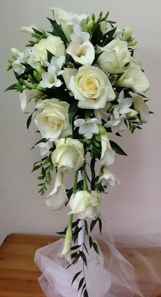 Brides shower bouquet of white Avalanche roses, calla lilies, freesia and trailing foliage.
