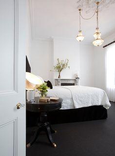 Dark grey carpet, crisp white bedroom with dark bed side table