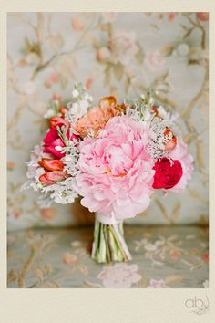 bright bouquet of peonies, roses, tulips and dusty miller. color combo of raspberry fizz, sweet blush, melon berry & soft stone