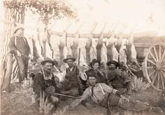 Six Wyoming hunters pose in front of nine antelope carcasses hung on a log that's supported by a tree and a wagon. Guns pictured in the 1906 photograph include a Model 1893 Marlin lever action rifle, a Model 1886 Winchester carbine and a Model 1895 Winchester lever action rifle.