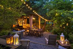 Jacqueline Ryan's backyard garden glows in the evening with strings of overhead lights, and candle-lit lanterns swinging from tree branches and grouped on tables. There is a table for dining and big couches for hanging out. (Mike Siegel/The Seattle Times)