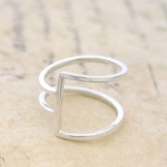 Simple and stylish, this geometric ring is handcrafted with sterling silver wire creating a contemporary, on-trend piece! Modern and abstract with a designer edge.For help with your ring size, copy…MoreMore  #SilverJewelry