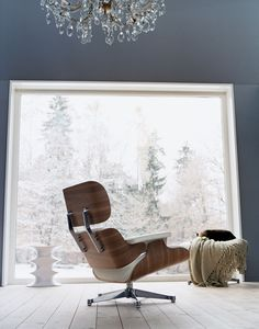 Snow outside. White Version of Eames Lounge Chair by Vitra inside.