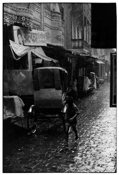 Boy running down a wet street in rain.. From Duke Digital Collections. Collection: William Gedney Photographs and Writings. Mark: None. Date of print: Unknown.