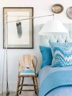 A framed feather art print sits over a rustic chair to the left of the bed. The modern arc light with it's giant shade is all that's needed to illuminate the bed at night.