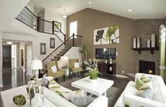 This gorgeous living room features a unified color palette, courtesy of deep brown flooring, white sofas, and light green splashes throughout. The addition of subtly colored throw pillows bring the white furniture to life.