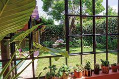 """Un jardín diseñado con objetos reciclados  El vidrio repartido fue fundamental para articular con el exterior. """"Vivimos en este lugar: es living y comedor, acá jugamos, trabajamos, estudiamos. Como da al sur, el sol no molesta"""".  Foto:Living /Daniel Karp"""