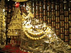 """Barney's 2010 Holiday Window Display - """"Have a Foodie Holiday"""" featuring """"Miss Illy"""". Miss Illy is made of 300 three-kilo illy tins, 250 foil bags (former home to illy's single-serve iperEspresso capsules) and 250 8.8-oz. illy cans. She wears an espresso machine headpiece (ahem, illy's Francis Francis X1 iperEspresso machine), a coffee scoop-turned earring and a garland fashioned from 300 paper cups."""