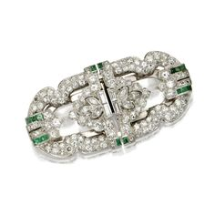 DIAMOND AND EMERALD DOUBLE-CLIP/BROOCH, CIRCA 1930 Of buckle design, the modified oblong-shaped brooch separating into a pair of shield-shaped clips, set with numerous old European-cut, single-cut, marquise-shaped and baguette diamonds weighing approximately 3.15 carats, accented with calibré-cut emeralds, mounted in platinum.
