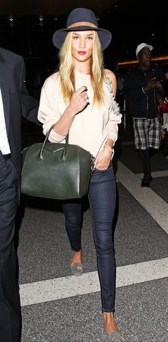Rosie Huntington-Whiteley in a Christopher Kane off-the-shoulder blouse, jeans, Janessa Leone hat, and hunter green Givenchy bag