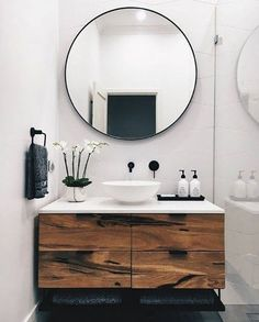 Below we see a striking round mirror with a gorgeous black frame that complements the tones and colour palette of this modern bathroom. It is eye-catching and visually appealing above a beautiful rustic wooden vanity. Contemporary and sophisticated – a stunning feature in any bathroom. #bathroomimprovements
