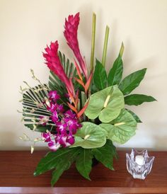 Designer selected trio of beautiful long lasting colorful tropical flowers. May include orchids, ginger, and anthurium as pictured or designer's choice. If you would like specific flowers or colors, please specify when ordering.  This is an ideal choice for corporate spaces and restaurants - or for anyone who loves tropicals! $85.00