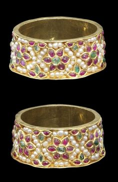 A pair of gem-set gold Bangles  India, early 20th Century of rounded form, the exterior with rubies and emeralds in raised gold floral settings, strung seed pearls in the interstices, the interior plain gold