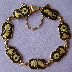 This lovely bracelet consists of seven linked settings claw-mounted with a panel of black enamel. The pieces are inlaid with beautiful gold floral and exotic bird designs.